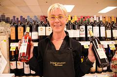 Frau im Supermarkt mit Weinflaschen